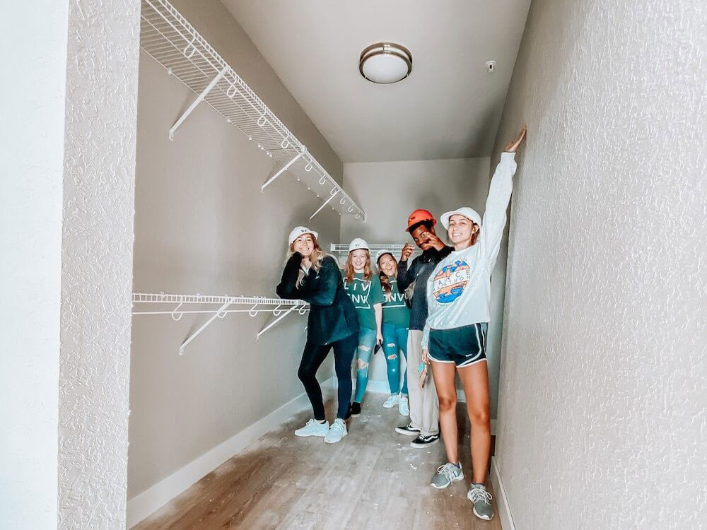 Five People Posing for a Picture in a Closet of an Apartment at Liv+ Gainesville